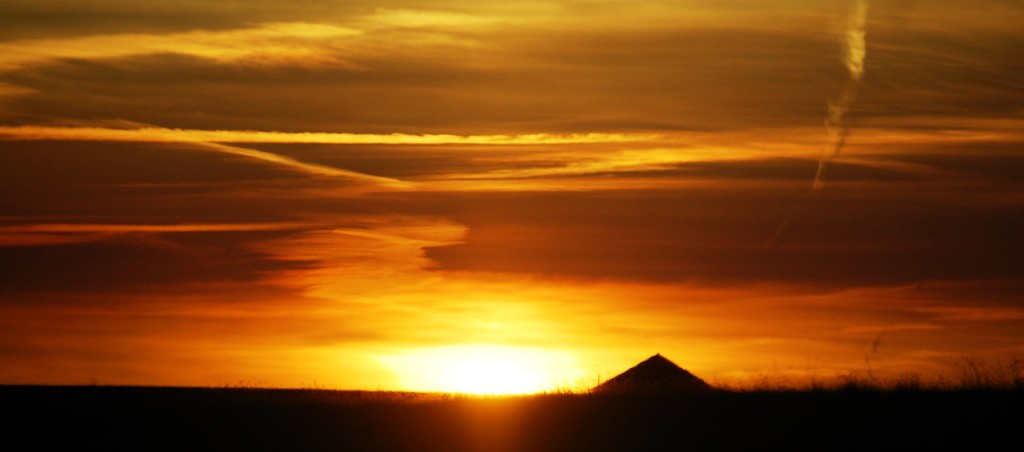 The roof of a barn is silhouetted in the sunset east of Glasgow, MT on US Route 2