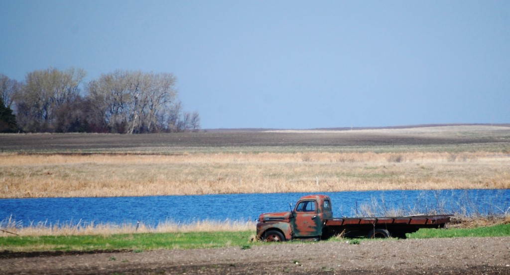 An old truck rests by one of the many ponds along ND Highway 1