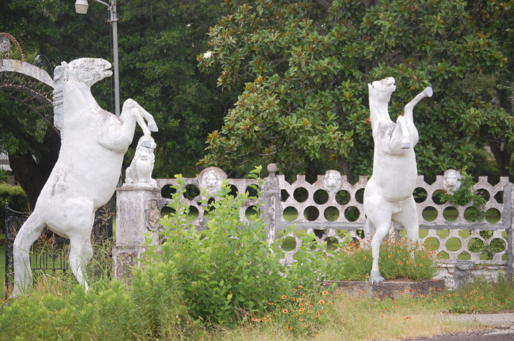 White Stallions guard the front gate of the Pignataro Castle in Santa Fe, Texas