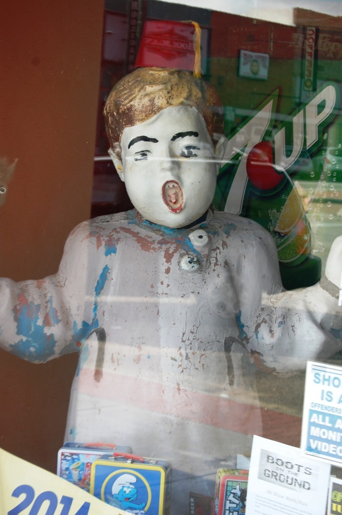 Old retro statue of a boy in the window at Atomic Candy in Denton, TX