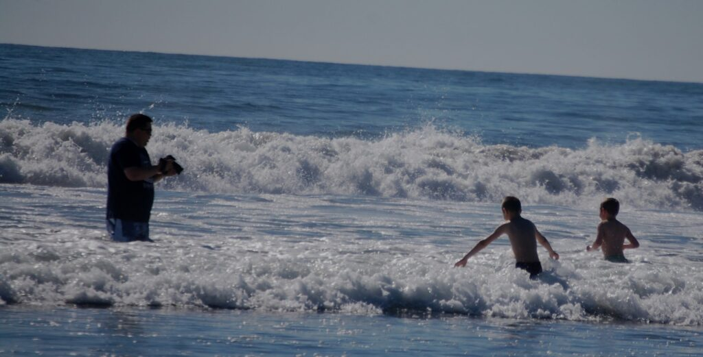 My son in law Aaron and my grandkids play in the ocean