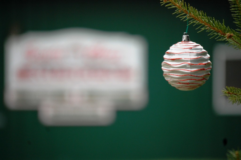 An ornament adorns a branch on a tree in front of the Santa Claus Museum
